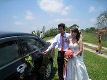 Groom open the car door for the bride Stock Photography