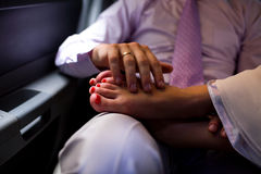 The groom pats the tired feet of his bride in the limo. Wedding moments Royalty Free Stock Photography