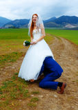 Groom peeking under his bride dress - funny wedding concept. Royalty Free Stock Images