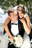 Groom pickaback his bride Royalty Free Stock Images