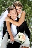 Groom pickaback his bride Stock Image