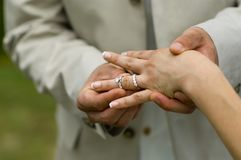 Groom placing engagement ring Royalty Free Stock Images