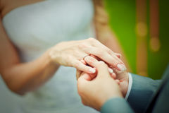 Groom placing an engagement ring Stock Image