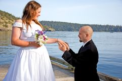 Groom Placing Ring on Bride's Finger. This groom is on his knees putting the ring on his young bride's finger on a dock in a beautiful ocean setting Royalty Free Stock Photography