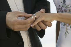 Groom placing ring on brides finger (close-up) stock image