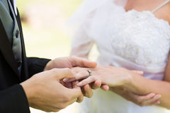 Groom placing ring on brides finger Stock Photo
