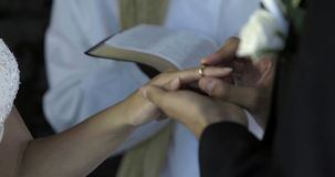 Groom placing ring on brides finger in front of priest stock video footage