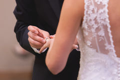 Groom placing wedding band on brides finger. After saying I do Stock Photo