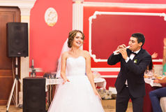 Groom playing a flute for his bride. Wedding party Stock Images