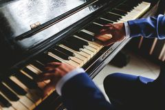 The groom plays the piano. Fingers on the keys stock images