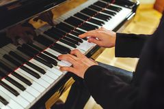 The groom plays the piano. The groom in a black suit plays the piano, fingers on the keys royalty free stock image