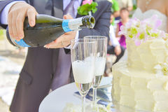 The groom pouring champagne to the glass Stock Photography