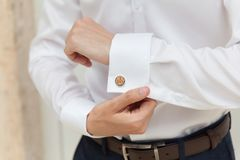 Groom prepares for wedding, shirt and cufflink. Groom prepares for wedding, cufflink I do on the sleeve stock image