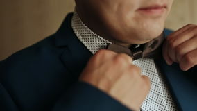 Groom is preparing for his wedding in the morning. The groom straightens his bow tie closeup. Groom is preparing for his wedding in the morning. The groom stock video footage