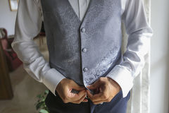 The groom is preparing for the wedding with waistcoat tait Stock Image