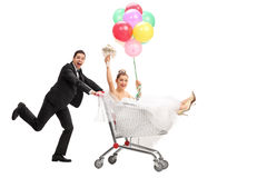 Groom pushing the bride in a shopping cart Stock Photos