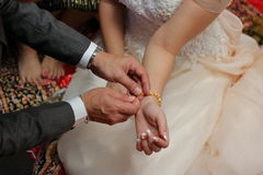 Groom put the gold bracelet on bride`s wrist. Concept of marriage Royalty Free Stock Photos