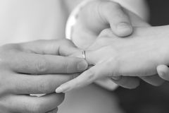 Groom put a ring on bride finger. Groom put an engagement ring on bride finger Royalty Free Stock Photo