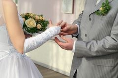 Groom put ring on bride`s finger Royalty Free Stock Photo