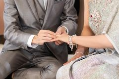 The groom put a wedding ring into a bride finger inThai Wedding. Concept stock photography