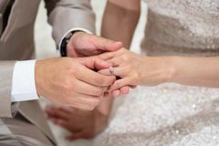 The groom put a wedding ring into a bride finger inThai Wedding. Concept royalty free stock image