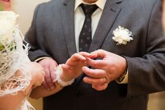 Groom put the wedding ring on bride`s finger. Close up Royalty Free Stock Photo