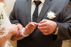 Groom put the wedding ring on bride`s finger. Close up Stock Photos