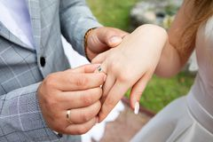 Groom put the wedding ring on bride`s finger. Close up royalty free stock image