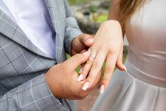 Groom put the wedding ring on bride`s finger. Close up royalty free stock photography