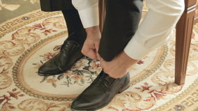 The groom puting shoes on and ties shoelaces stock video footage