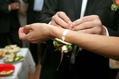 Groom puts on the bride's hand flower decoration Royalty Free Stock Photo
