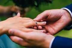 Groom puts bride a wedding ring of gold on his finger Royalty Free Stock Photo