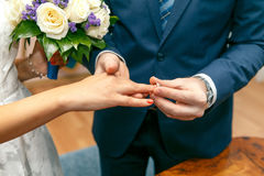 The groom puts on an engagement ring on the finger of the bride. The groom puts on an engagement ring on the bride`s finger.Horizontal photo Royalty Free Stock Photo