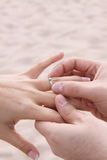 Groom puts ring on Bride - Beach Wedding. Husband and wife's hands with wedding ring. Groom puts band on brides finger Royalty Free Stock Image