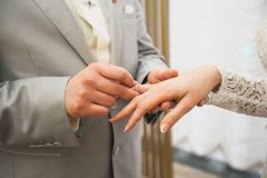 The groom puts the ring on the bride`s hand. Hands of the newlyweds on the wedding day, close-up. The exchange of rings during th royalty free stock images