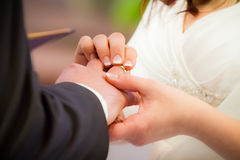 Groom puts ring on brides finger Stock Photography