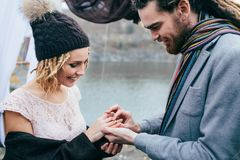 Groom puts a ring on the finger of the bride. Autumn wedding ceremony outdoors. Newlyweds with dreadlocks look at each. Other standing near bridal arch. Close Royalty Free Stock Image