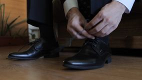 Groom puts on shoes and tying shoelaces stock video