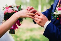 Groom puts a wedding ring on the bride`s finger. At the wedding ceremony Stock Images