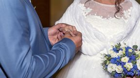 Groom puts a wedding ring on the bride`s finger, newlyweds, bouq. Uet, couple, man and woman, wedding, hands, Bridal bouquet Stock Images