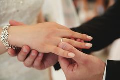 The groom puts a white gold engagement ring on his finger. The groom puts on a finger wedding ring in white gold, close-up Stock Photo