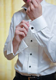A groom putting on cuff-links as he gets dressed Royalty Free Stock Images