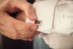 Groom putting on cuff-links as he gets dressed Royalty Free Stock Images