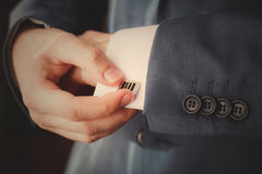 Groom putting on cuff-links as he gets dressed Stock Images