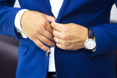 Groom putting on cuff-links as he gets dressed in formal wear. Close up royalty free stock images