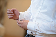 Groom is putting on the cufflink Stock Photos