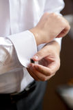 Groom is putting on the cufflink Royalty Free Stock Photos