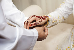 Groom putting on a gold chain into the hands of the bride Royalty Free Stock Image