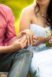 Groom putting golden ring in brides hand at park Royalty Free Stock Photo