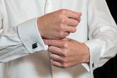 Groom putting on his cufflinks Stock Photo